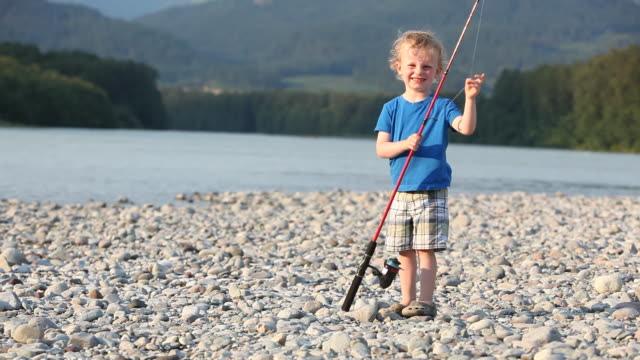 Caucasian boy holding fishing pole by river