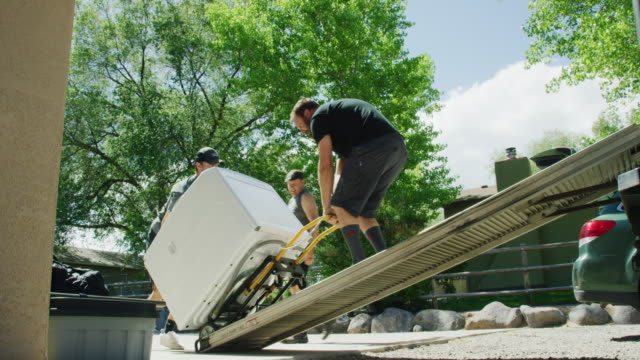vídeos de stock e filmes b-roll de a caucasian boy in his late teens helps to push a clothes washing machine on a dolly/hand truck up a ramp and into the back of a moving truck while a caucasian man in his forties pulls the dolly on a sunny day - mobília