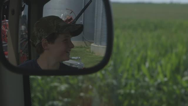 Caucasian boy laughing in farm truck