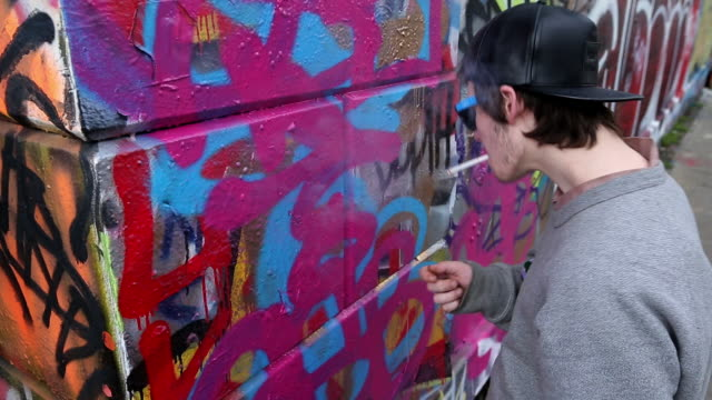 caucasian boy painting graffiti on wall - un ragazzo adolescente video stock e b–roll