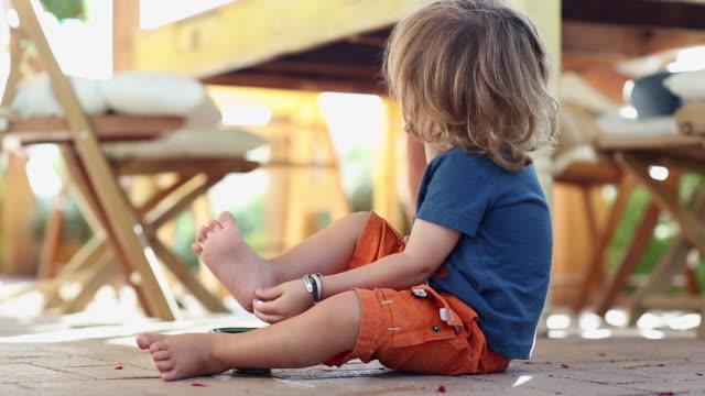 vídeos y material grabado en eventos de stock de caucasian boy playing on patio - descalzo