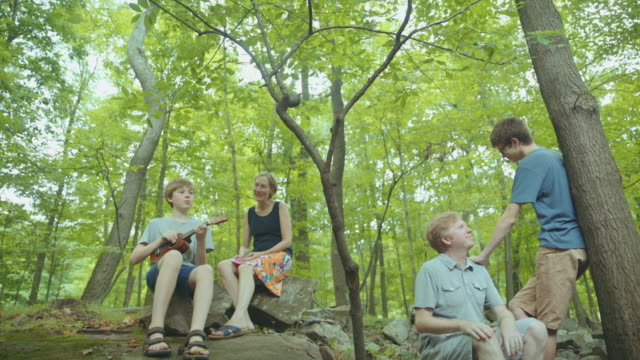 Caucasian boy playing ukulele for family in forest