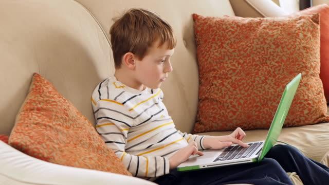 Caucasian boy using laptop on sofa