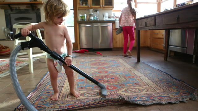 Caucasian boy vacuuming rug