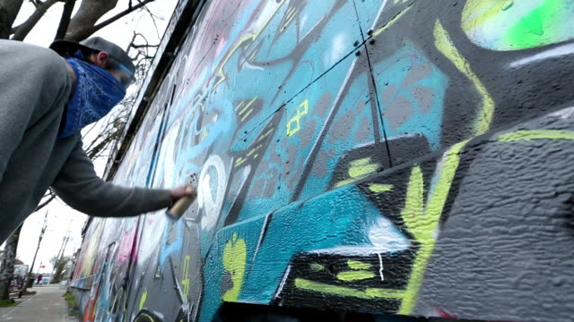 caucasian boy with bandana painting graffiti on wall - graffiti stock videos & royalty-free footage