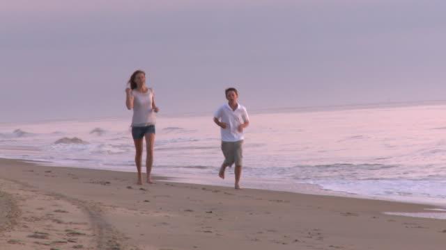 Caucasian brother and sister jogging toward camera along beach at sunrise