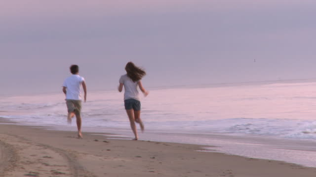 Caucasian brother and sister racing away from camera along beach at sunrise