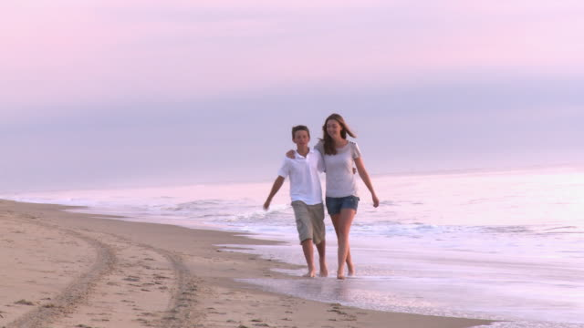 vídeos y material grabado en eventos de stock de caucasian brother and sister walking toward camera along beach at sunrise - descalzo