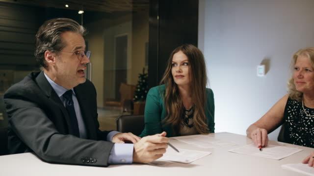 vidéos et rushes de un homme d'affaires caucasien dans la cinquantaine s'entretient avec ses collègues d'âges variables autour d'une table de conférence dans une salle intérieure du conseil d'administration - gouvernement