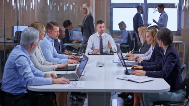 ds caucasian business man leading a meeting with his colleagues in the glass conference room - business conference stock videos & royalty-free footage