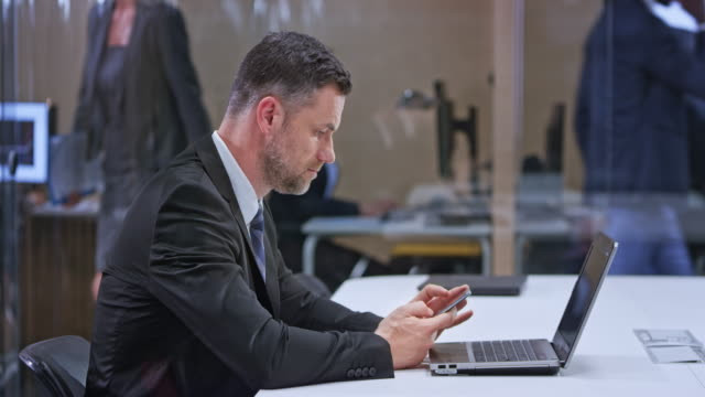 ds caucasian business man sitting in the glass conference room with his laptop open and checking his mobile phone - text stock videos & royalty-free footage