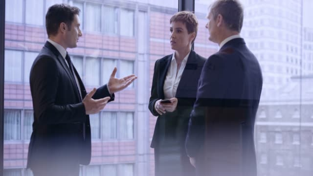 caucasian business man talking to a senior business man and a business woman in the glass office downtown - corridor stock videos & royalty-free footage