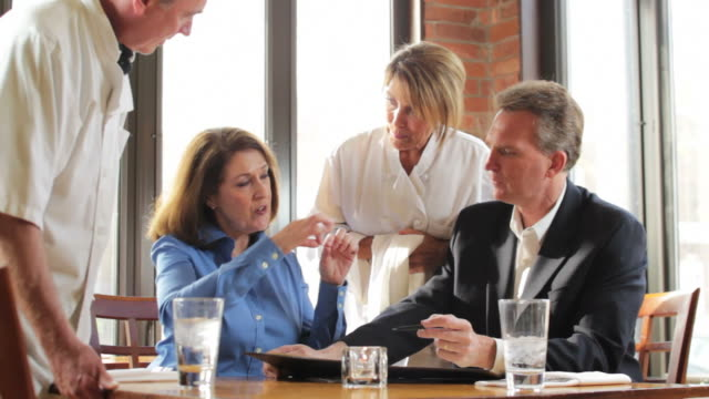 Caucasian business people discussing menu with chefs at restaurant