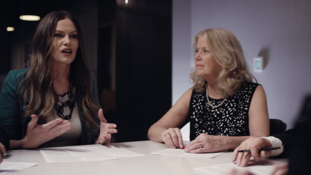 a caucasian business woman in her forties discusses paperwork with her colleagues at a conference table in a board room indoors - conference table stock videos & royalty-free footage
