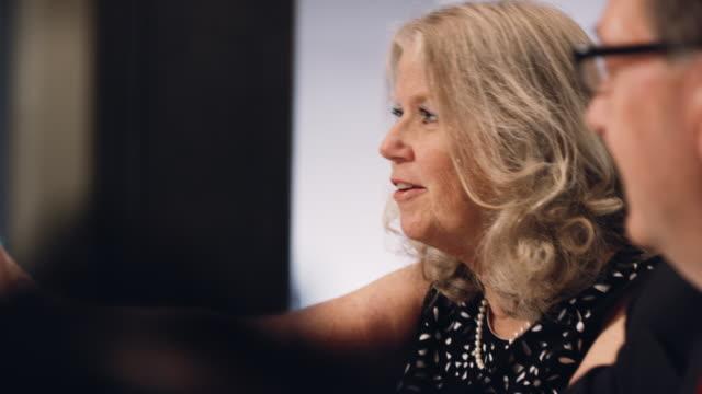 60代の白人ビジネスウーマンが笑顔で、役員室で同僚と話す - 会議用テーブル点の映像素材/bロール
