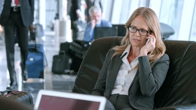 空港のビジネス ラウンジで電話で話して ds 白人ビジネス女性 - ロビー点の映像素材/bロール