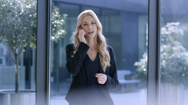 Caucasian business woman with blonde hair talking on the phone in the hallway of a modern business building