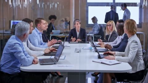 ds caucasian business woman with dark hair leading a meeting in the glass conference room - expertise stock videos & royalty-free footage