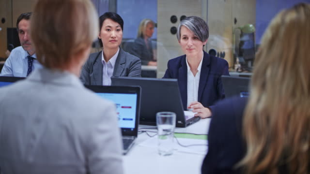 caucasian business woman with grey hair leading a meeting in the conference room - navy blue stock videos & royalty-free footage