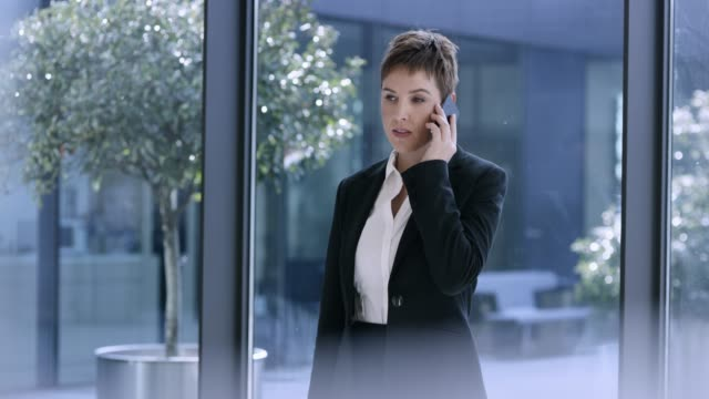 caucasian business woman with short hair talking on the phone in the hallway of a modern business building - 30 39 years stock videos & royalty-free footage