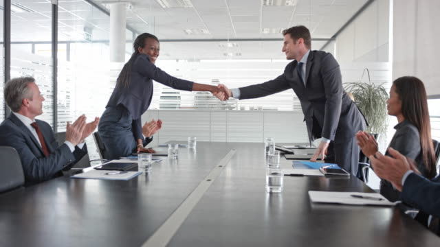 caucasian businessman and african-american businesswoman signing a contract and shaking hands in front of colleagues in the conference room - sala conferenze video stock e b–roll