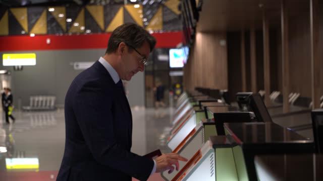caucasian businessman at the airport printing boarding pass on kiosk smiling - biglietto aereo video stock e b–roll