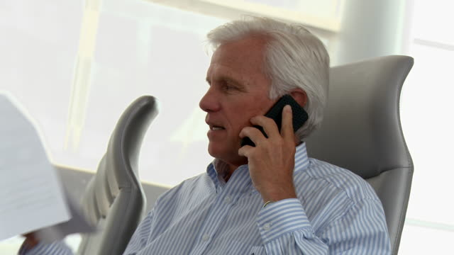 Caucasian businessman holding paperwork talking on cell phone