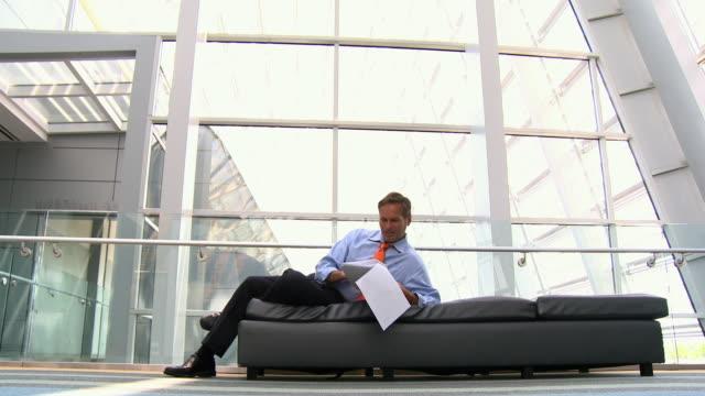 stockvideo's en b-roll-footage met caucasian businessman laying on bench in atrium reading paperwork - overhemd en stropdas