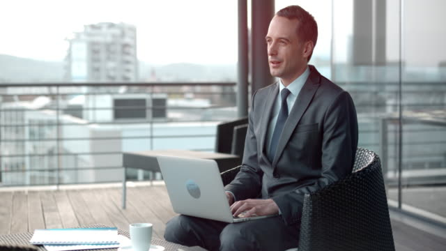 都市の屋上テラス ラウンジで彼のラップトップに取り組んでいる間熟考白人実業家 - トップス点の映像素材/bロール