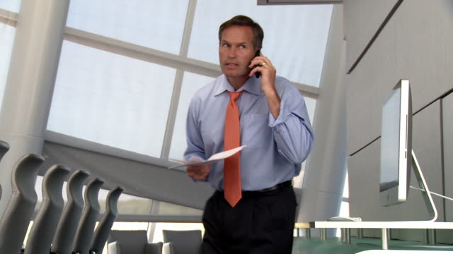 Caucasian businessman reading paperwork and using cell phone