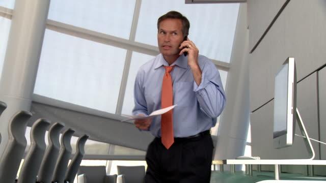 vídeos y material grabado en eventos de stock de caucasian businessman reading paperwork and using cell phone - camisa y corbata