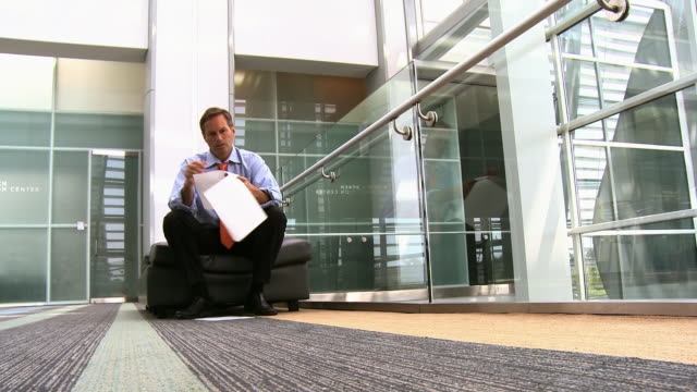 vídeos de stock, filmes e b-roll de caucasian businessman reading paperwork in atrium - camisa e gravata