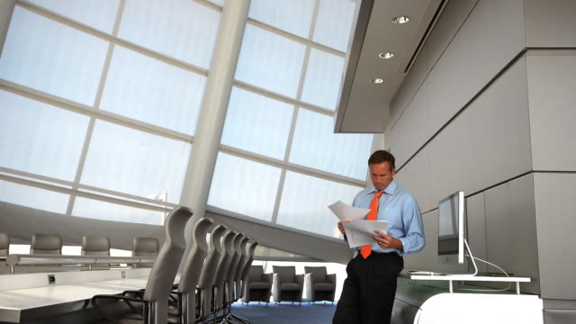 Caucasian businessman reading paperwork in conference room