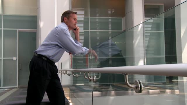 stockvideo's en b-roll-footage met caucasian businessman talking and texting on cell phone - overhemd en stropdas