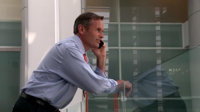 Caucasian businessman talking on cell phone in atrium