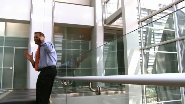 stockvideo's en b-roll-footage met caucasian businessman talking on cell phone in atrium - overhemd en stropdas