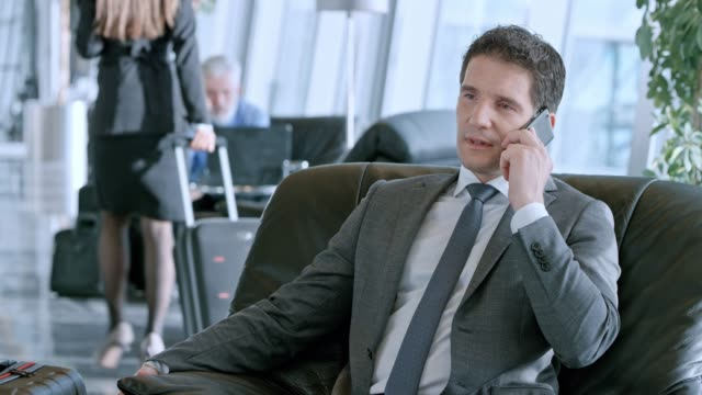 ds caucasian businessman talking on the phone in the business lounge at the airport - sala d'imbarco video stock e b–roll