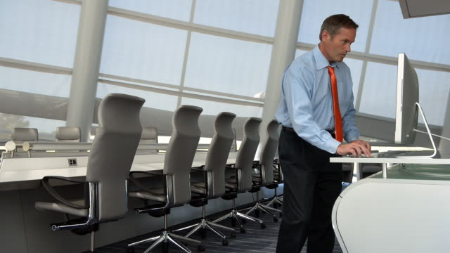 Caucasian businessman using computer in conference room