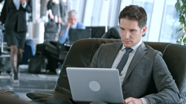 ds caucasian businessman working on his laptop at the airport in the business lounge - gate stock videos & royalty-free footage