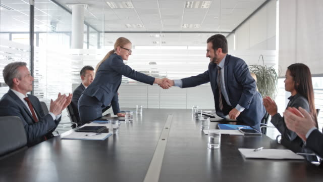 Caucasian businesswoman and businessman signing a contract and shaking hands and their two teams applaud in the conference room