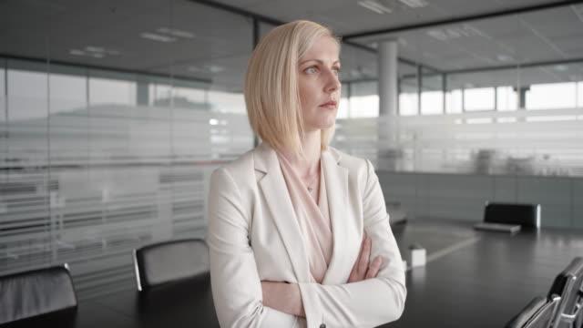 kaukasische geschäftsfrau im konferenzraum grübeln und blick in die kamera - kurzes haar stock-videos und b-roll-filmmaterial