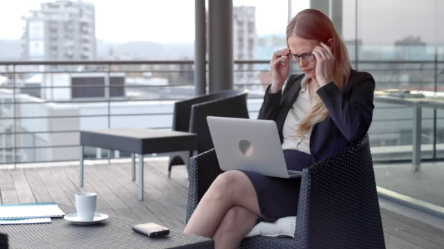 caucasian businesswoman pondering while working on her laptop in the terrace lounge overlooking the city - cross legged stock videos & royalty-free footage