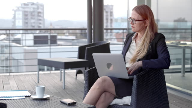 caucasian businesswoman with glasses working on her laptop in a rooftop lounge in the city - blonde hair stock videos & royalty-free footage