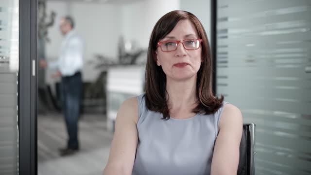 vídeos de stock, filmes e b-roll de empresária caucasiana com óculos vermelhos em uma chamada de conferência de vídeo do escritório dela - sentando