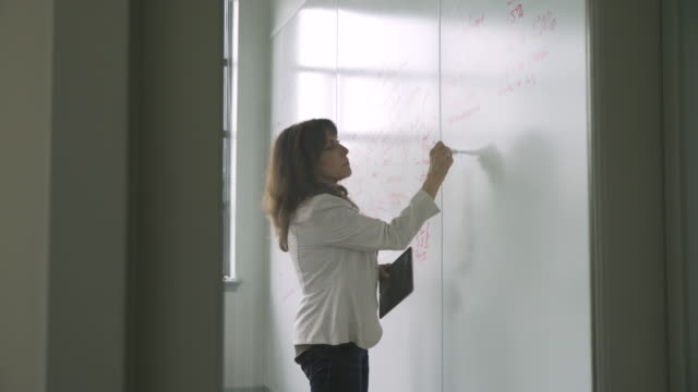 Caucasian businesswoman writing on whiteboard in meeting behind door