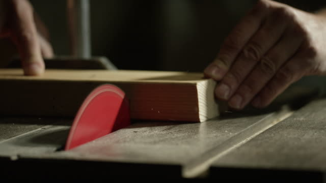 a caucasian carpenter uses a table saw to cut through a wooden board - sawdust stock videos and b-roll footage