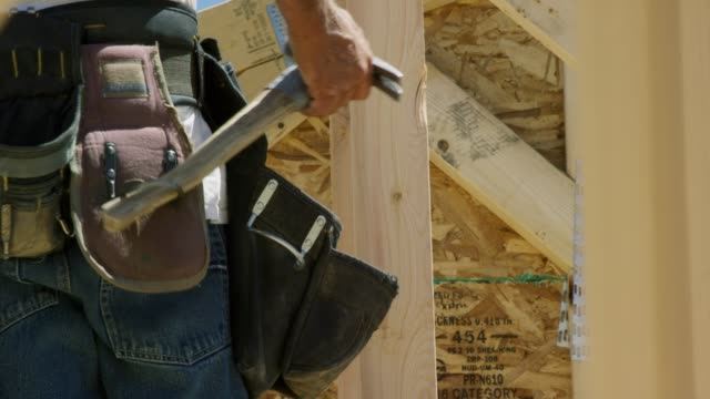 a caucasian construction worker puts his hammer from his tool belt while framing a house on a sunny day - tool belt stock videos and b-roll footage