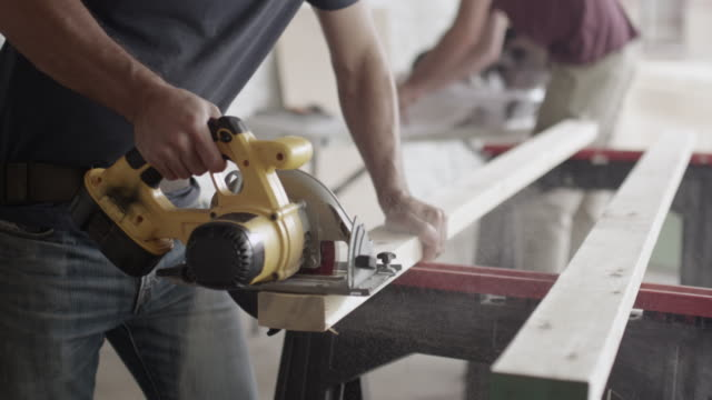 Caucasian construction worker sawing wood