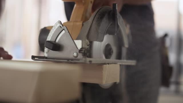 vídeos de stock, filmes e b-roll de caucasian construction worker sawing wood - serra circular