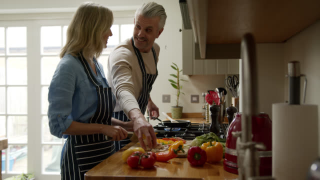caucasian couple at home cooking together while talking and smiling - mature couple stock videos & royalty-free footage